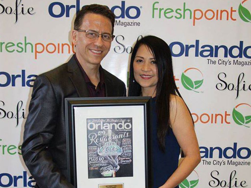 The owner of Thai Blossom Restaurant receiving the award from Orlando Magazine